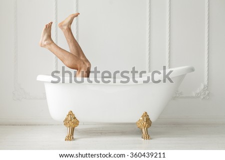 The naked feet which are looking out of a white bath in a white interior. White bath. The naked feet. White interior. - stock photo