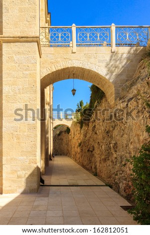 The narrow archway and pedestrian bridge along the walls - stock photo