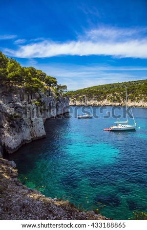 The narrow fjords between the rocky shore. White sailing boats waiting for tourists. National Park Calanques on the Mediterranean coast - stock photo