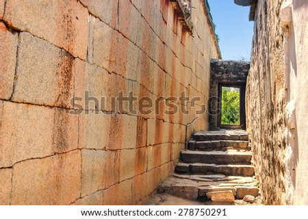 The narrow old street with the ladder conducting to an open door with green foliage inside, Hampi, India - stock photo