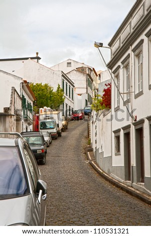 The narrow street on a steep slope with parked cars - stock photo