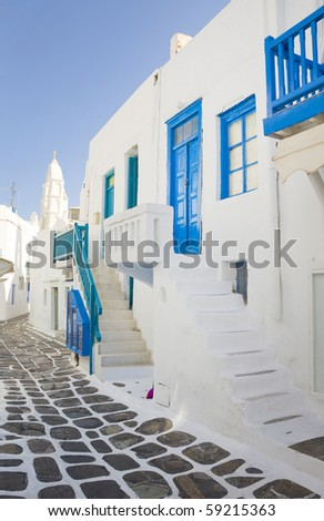The narrow street with colored sidewalk and stairs around houses and churches - is typical of the Greek islands. Mykonos. - stock photo
