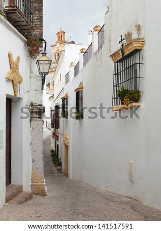 The narrow street with old houses, Arcos de la Frontera, Andalusia, Spain. - stock photo