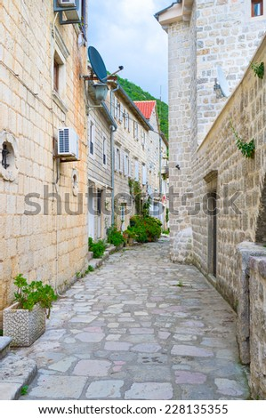 The narrow winding street with white stone houses, located at the foot of the mountain, Perast, Montenegro. - stock photo