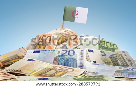 The national flag of Algeria sticking in a pile of mixed european banknotes.(series) - stock photo