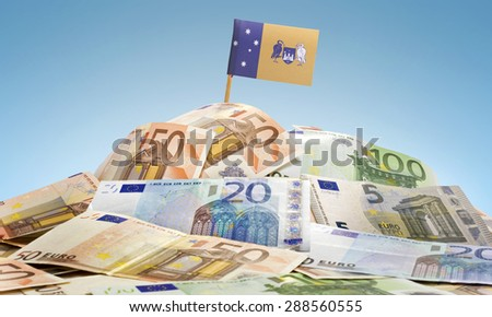 The national flag of Australian Capital Territory sticking in a pile of mixed european banknotes.(series) - stock photo