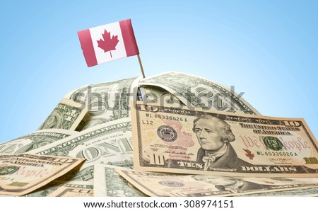 The national flag of Canada sticking in a pile of american dollars.(series) - stock photo