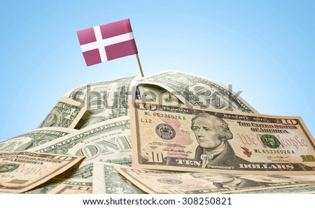 The national flag of Denmark sticking in a pile of american dollars.(series) - stock photo
