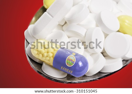 The national flag of Kansas on a capsule and pills on a spoon.(series) - stock photo