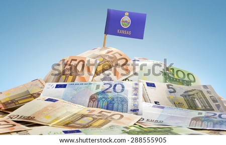 The national flag of Kansas sticking in a pile of mixed european banknotes.(series) - stock photo