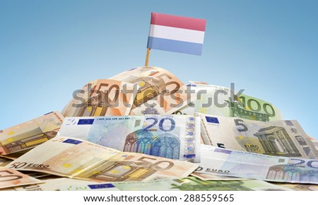 The national flag of Luxembourg sticking in a pile of mixed european banknotes.(series) - stock photo