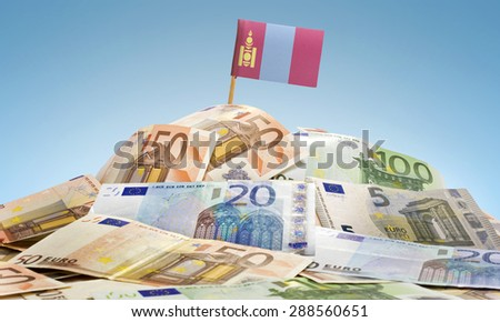 The national flag of Mongolia sticking in a pile of mixed european banknotes.(series) - stock photo