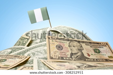 The national flag of Nigeria sticking in a pile of american dollars.(series) - stock photo