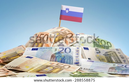 The national flag of Slovenia sticking in a pile of mixed european banknotes.(series) - stock photo