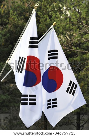 The national flag of South Korea. It has three parts: a white background, a red and blue Taeguk, which is a red and blue Taiji yin- and yang-symbol in the center.