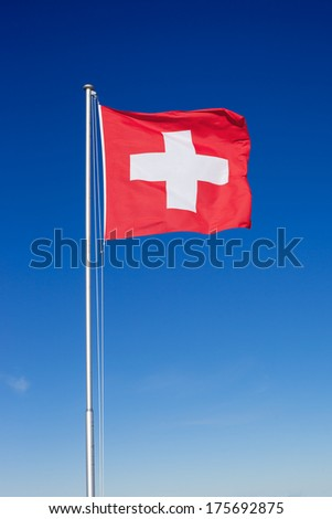 The national flag of Switzerland flying on a metal pole against a clear blue sky. - stock photo