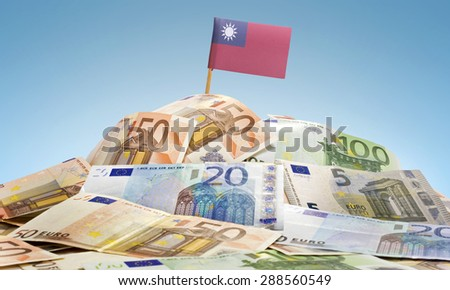 The national flag of Taiwan sticking in a pile of mixed european banknotes.(series) - stock photo