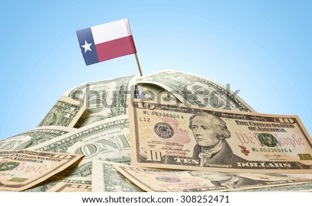 The national flag of Texas sticking in a pile of american dollars.(series) - stock photo