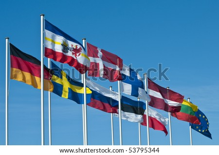 The National flags of the states around the Baltic Sea and the  flag of the European Union flying in the wind in front of a clear blue sky. - stock photo