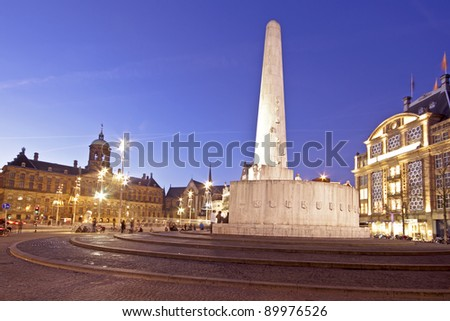 The National Monument on the Dam and in the background the Royal Palace in Amsterdam the Netherlands at twilight - stock photo
