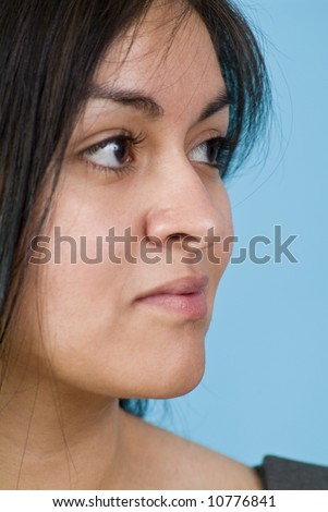 The natural beauty of a young Hispanic woman captured in a closeup portrait. - stock photo