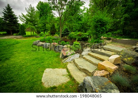 The natural stone steps of a stairway garden feature climb a small hill in a lush, green summer rock garden. - stock photo