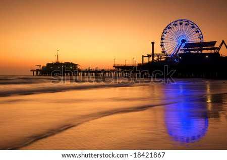 The Neon lit Ferris Wheel of Santa Monica Pier is reflected in the wet sand of the beach at Sunset. - stock photo
