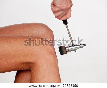 The neurologist testing knee reflex on a female patient using a hammer - stock photo
