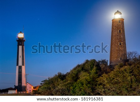 The New and Old Cape Henry Lighthouses. With full moon behind the Old. - stock photo