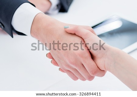 The new deal. Confident and successful two businessmen shaking hands at the signing. The man shakes hands with a woman at business lunch - stock photo
