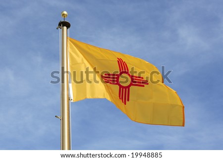The New Mexico state flag against a frosty blue sky. - stock photo