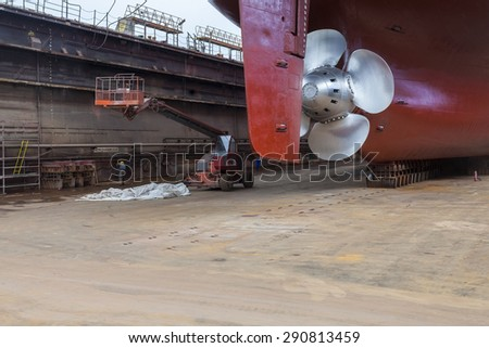 "The new propeller mounted on a refurbished ship. The inscription on the dock reads: ""welding waste storage locations"". - stock photo"