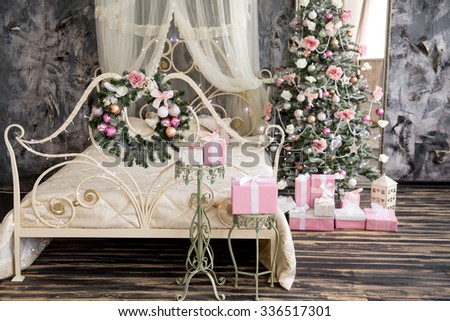 the New Year tree with pink urkasheniye costs near a bed, gifts - stock photo