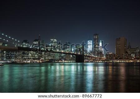 The New York City skyline at night w Brooklyn Bridge - stock photo