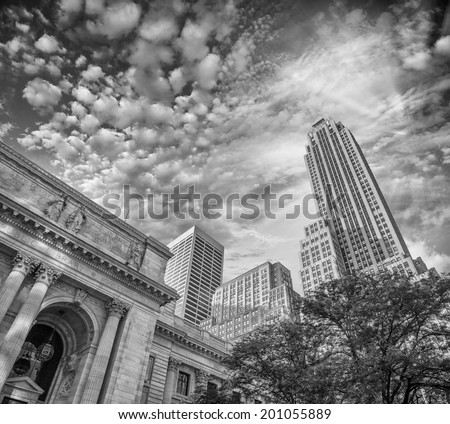 The New York Public Library at dusk, surrounded by trees and tall skyscrapers. - stock photo