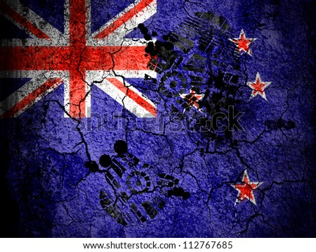 The New Zealand flag painted on  cracked ground with vignette with dirty oil footprint over it - stock photo