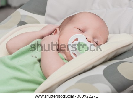 The newborn one-month baby falls asleep and sucks a baby's dummy - stock photo