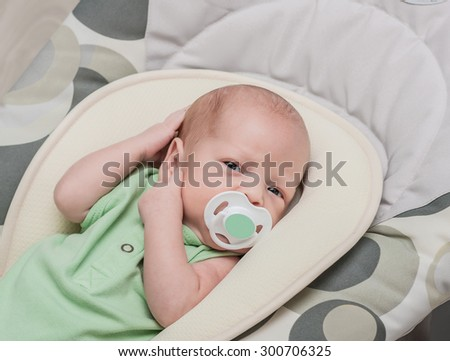 The newborn one-month baby lies and sucks a baby's dummy - stock photo