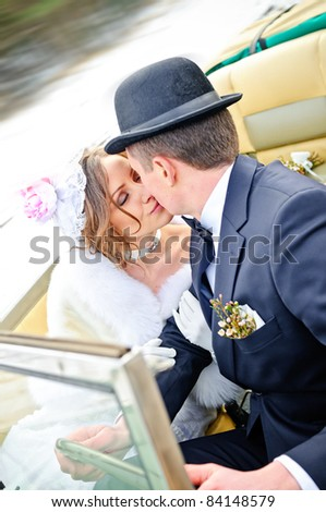 the newly married couple drive retro wedding car - stock photo