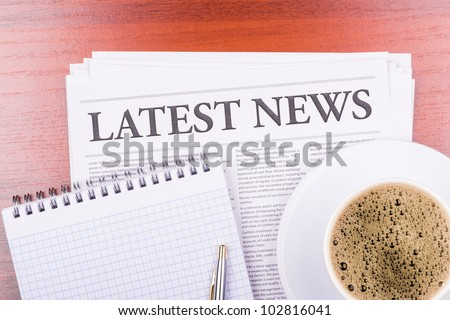 The newspaper LATEST NEWS on table  and coffee - stock photo
