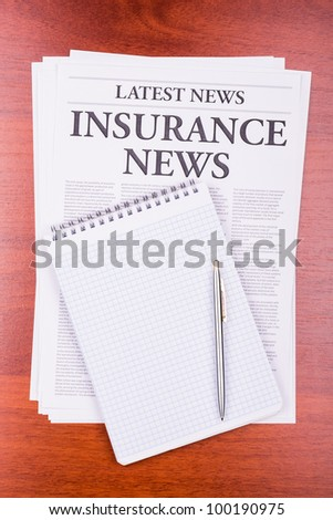 The newspaper LATEST NEWS with the headline INSURANCE NEWS and notepad