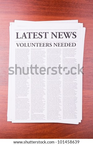 The newspaper LATEST NEWS with the headline VOLUNTEERS NEEDED - stock photo