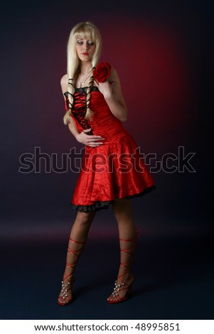 The nice blonde in a red satiny dress on a dark blue background