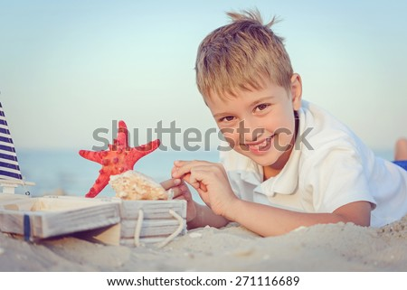 The nice boy on the seashore playing with cockleshells and a ship - stock photo