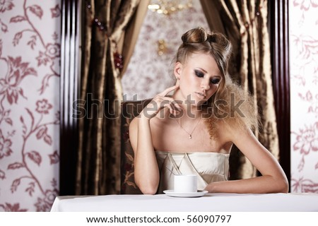 The nice girl behind a table with a cup in cafe - stock photo