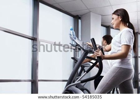 The nice girl is engaged in fitness club - stock photo