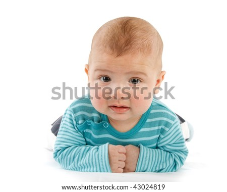 The nice small child in striped rompers lays on a stomach on a white background.