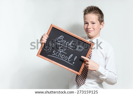 The nice smiling boy teenager in a white shirt and a tie on a grey background specifies a finger in the black chalkboard with inscription Back to school - stock photo