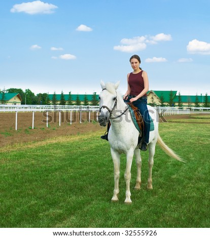 The nice young girl astride a horse on a hippodrome - stock photo