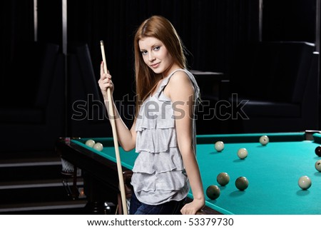 The nice young girl with cue at a billiard table - stock photo